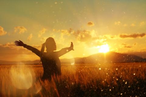 Woman with arms spread toward the horizon