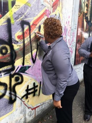 Rev. Kenya Lovell, Bethune-Cookman University, writes on peace wall in Belfast.